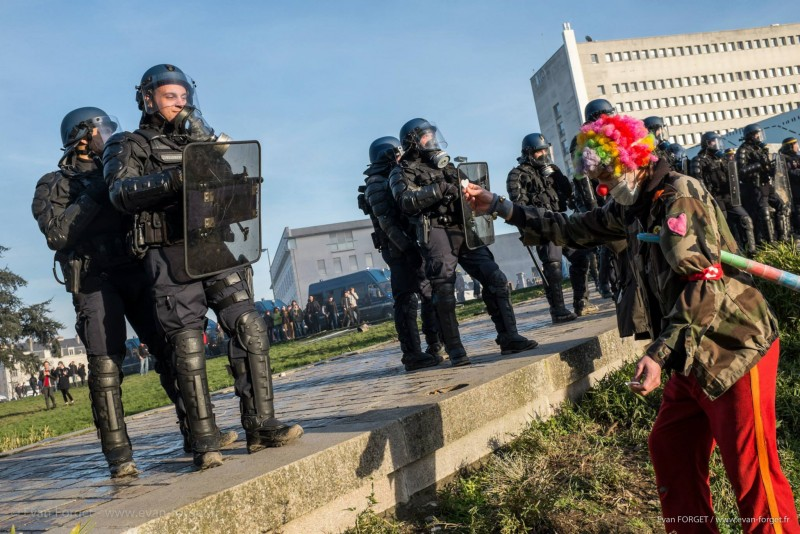 Un clown cherche à poser un coeur en papier sur le bouclier d'un gendarme / Nantes 2012